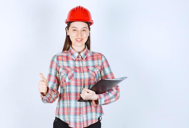 Młoda kobieta w kasku trzymającym czarny folder i pokazując kciuk do góry.