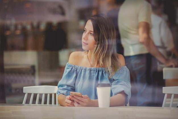 Młoda kobieta w kawiarni i picia kawy i korzystania z telefonu komórkowego, siedząc przy oknie