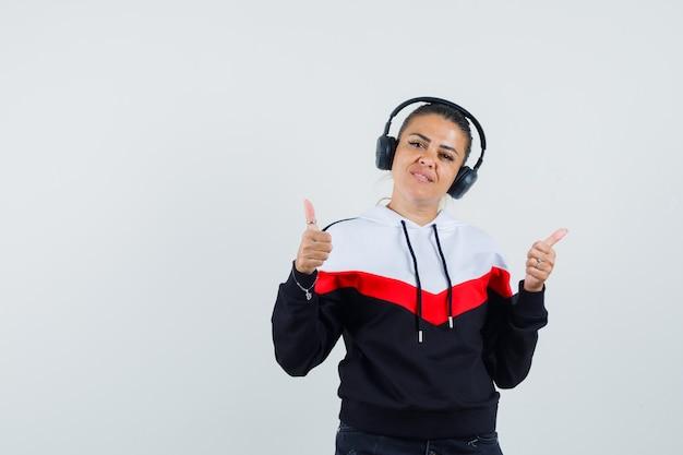 Młoda kobieta w kolorowej bluzie, słuchawki pokazujące kciuk w górę podczas słuchania muzyki i wyglądający na zadowolonego, widok z przodu.