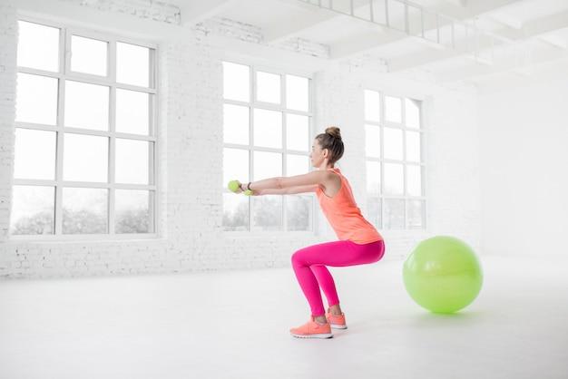 Młoda kobieta w kolorowej odzieży sportowej kuca z hantlami w białej siłowni z piłką fitness na podłodze