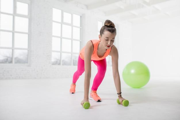 Młoda kobieta w kolorowej odzieży sportowej robi pompki z hantlami i piłką fitness w tle