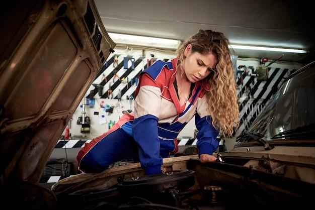 Młoda kobieta w kombinezonie w garażu naprawia auto.