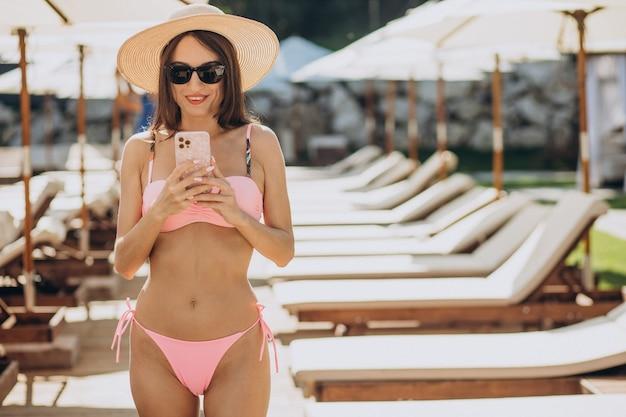 Młoda kobieta w kostiumie kąpielowym przy basenie