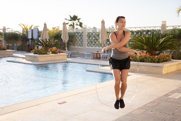 Młoda kobieta w koszulce i spodenkach skacze przez skakankę na dziedzińcu z basenem.