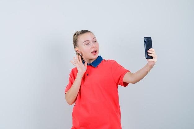 Młoda kobieta w koszulce, machając ręką na czacie wideo i patrząc radośnie