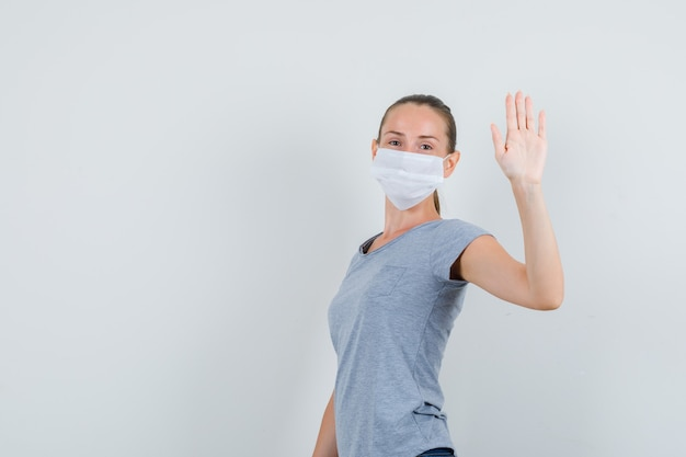 Młoda kobieta w koszulce, masce, dżinsach macha ręką, by się pożegnać i patrzy wesoło.