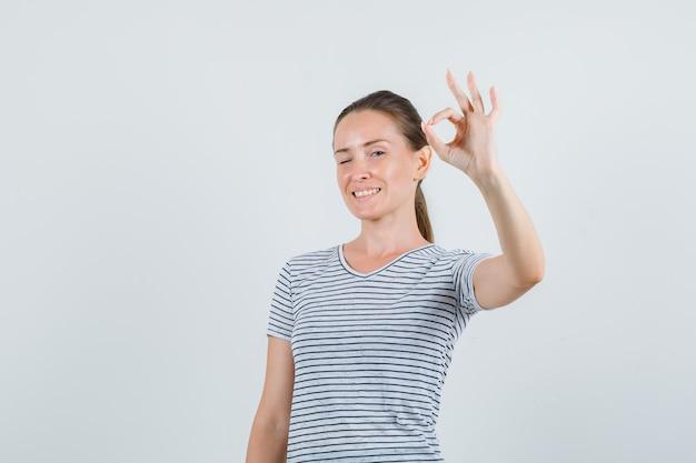 Młoda kobieta w koszulce pokazując gest ok i patrząc wesoło, widok z przodu.