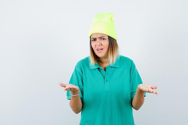 Młoda kobieta w koszulce polo, czapka pokazująca bezradny gest i patrząca zamyślona, widok z przodu.