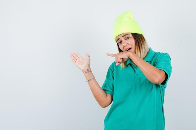 Młoda kobieta w koszulce polo, czapka skierowana w lewo, pokazująca powitalny gest i wyglądająca na zaskoczoną, widok z przodu.
