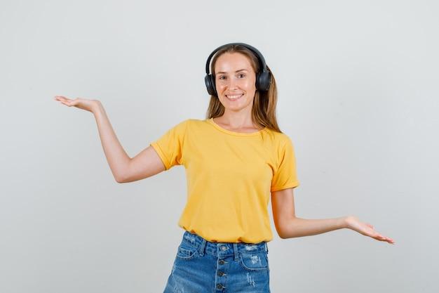 Młoda kobieta w koszulce, spodenkach, słuchawkach, podnosząc ręce, aby pokazać równowagę i zadowolony