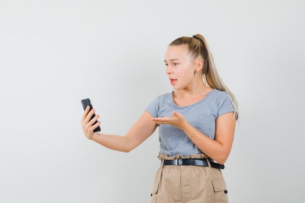 Młoda kobieta w koszulce, spodniach dyskutuje coś na czacie wideo i wygląda na zdezorientowanego, widok z przodu.
