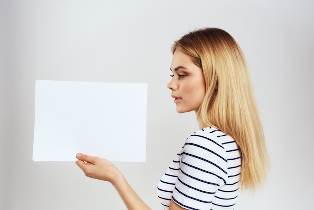 Młoda kobieta w koszulce trzyma czysty papier