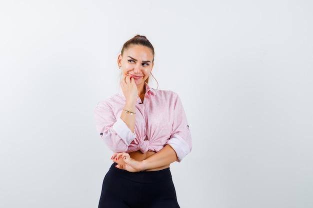 Młoda kobieta w koszuli casual, trzymając rękę na brodzie i patrząc zamyślony, widok z przodu.