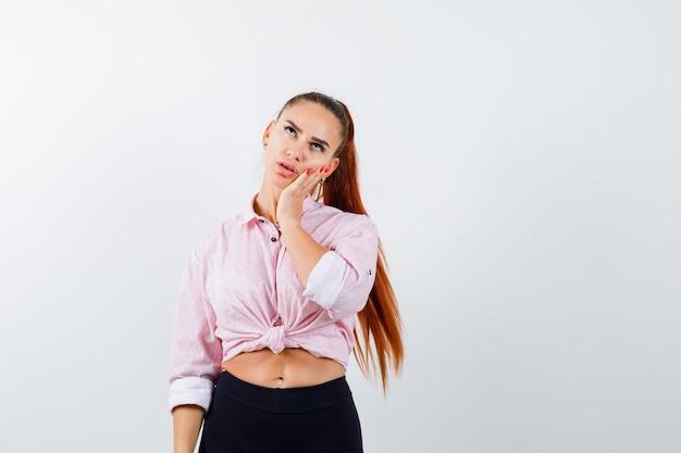 Młoda kobieta w koszuli casual, trzymając rękę na policzku i patrząc zamyślony, widok z przodu.