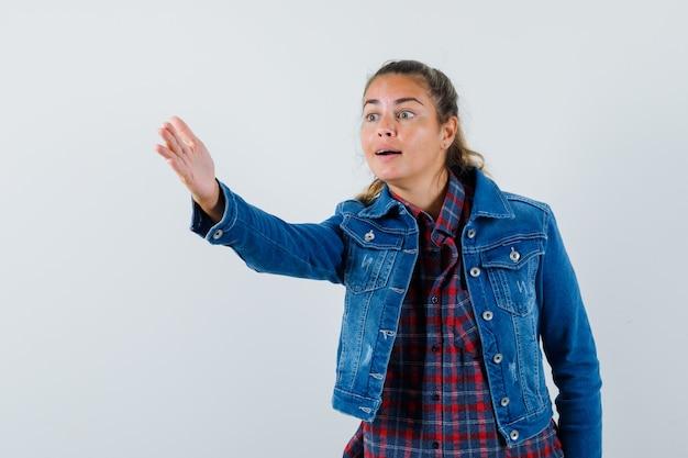 Młoda kobieta w koszuli, kurtce, dając instrukcje przez rozciąganie ręki, widok z przodu.