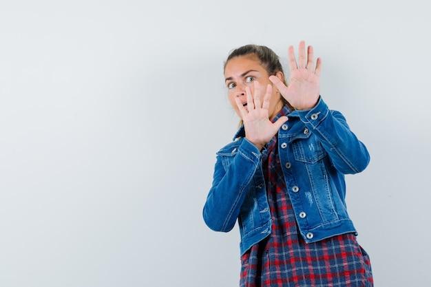 Młoda kobieta w koszuli, kurtce pokazując gest stopu i patrząc przestraszony, widok z przodu.