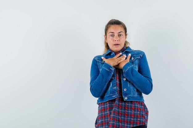 Młoda kobieta w koszuli, kurtce, trzymając się za ręce na piersi i patrząc zdziwiona, widok z przodu.