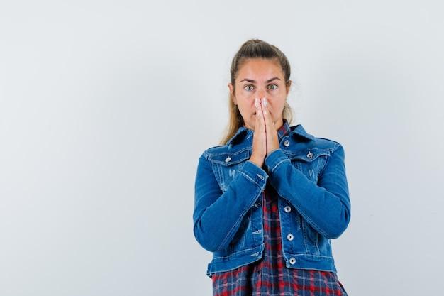 Młoda kobieta w koszuli, kurtce, trzymając się za ręce w geście modlitwy i patrząc zdziwiony, widok z przodu.