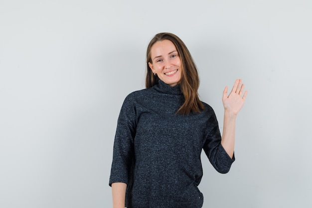 Młoda kobieta w koszuli macha ręką, by się pożegnać i patrzy wesoło