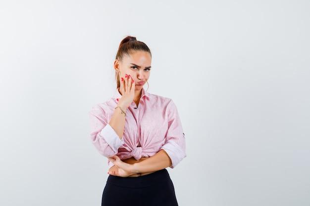Młoda kobieta w koszuli na co dzień, trzymając dłoń na policzku, wyginając usta i patrząc niepewnie, z przodu.