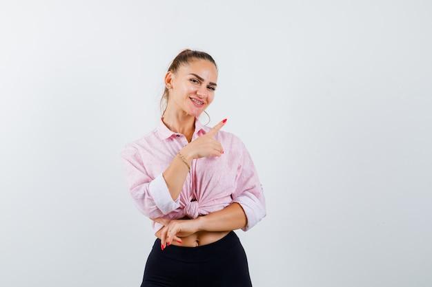 Młoda kobieta w koszuli na co dzień, wskazując na prawy górny róg i patrząc szczęśliwy, widok z przodu.