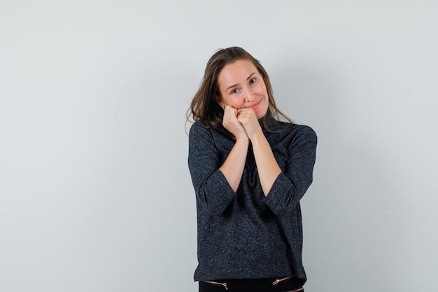Młoda kobieta w koszuli, opierając policzek na pięści i wyglądający pięknie