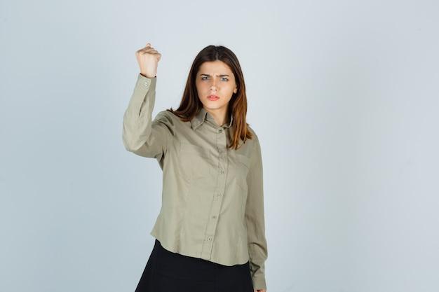 Młoda kobieta w koszuli, podnosząca zaciśniętą pięść w spódnicy i wyglądająca złośliwie