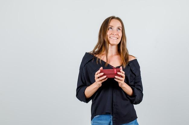 Młoda kobieta w koszuli, spodenki, patrząc z obecnym pudełkiem i patrząc zadowolony