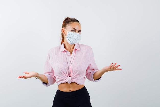 Młoda kobieta w koszuli, spodniach, masce medycznej, pokazując bezradny gest i patrząc nieświadomie, widok z przodu.