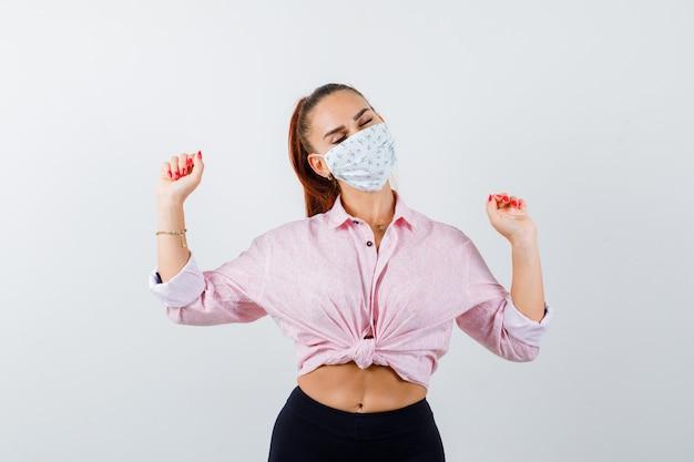 Młoda kobieta w koszuli, spodniach, masce medycznej pokazując gest zwycięzcy i patrząc na szczęście, widok z przodu.