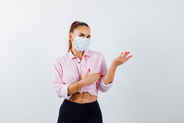 Młoda kobieta w koszuli, spodniach, masce medycznej wita coś i wygląda pewnie, widok z przodu.