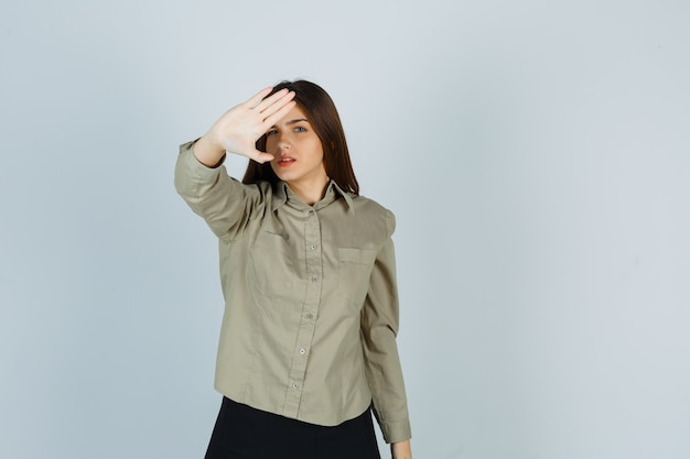 Młoda kobieta w koszuli, spódnica pokazując gest stop i patrząc zirytowany, widok z przodu.