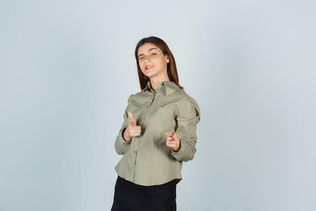 Młoda kobieta w koszuli, spódnica pokazuje gest pistoletu, mrugając i wyglądając pewnie