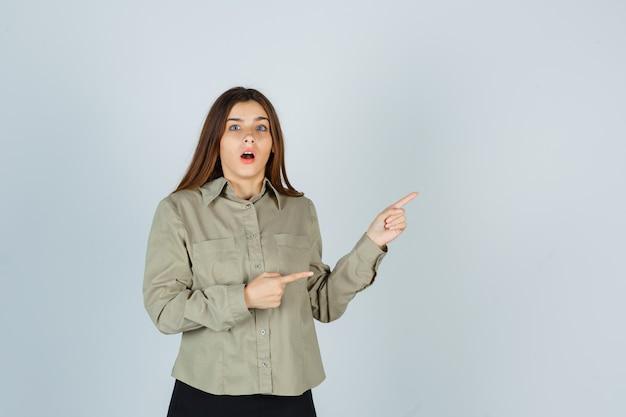 Młoda kobieta w koszuli, spódnica skierowana w prawy górny róg i wyglądająca na zdziwioną