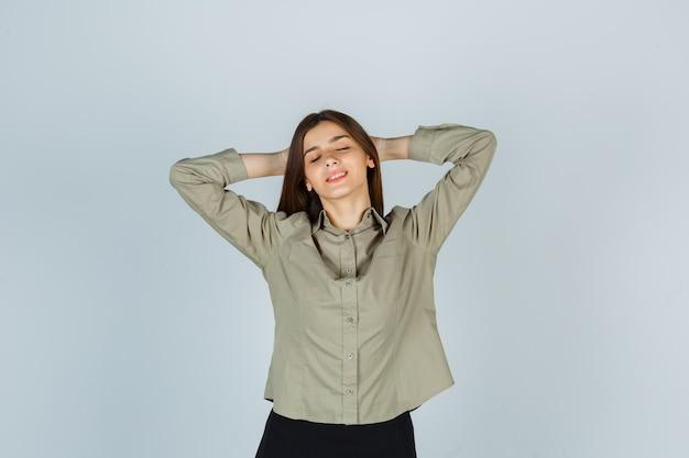 Młoda kobieta w koszuli, spódnica trzymając ręce za głową i patrząc zrelaksowany, widok z przodu.