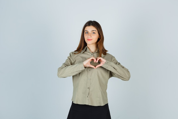 Młoda kobieta w koszuli, spódnicy pokazując gest serca i patrząc pewnie