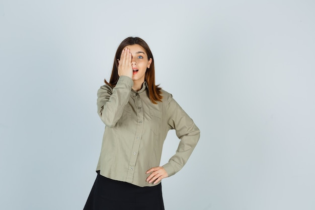 Młoda kobieta w koszuli, spódnicy trzymając rękę na oku i patrząc zdziwiona