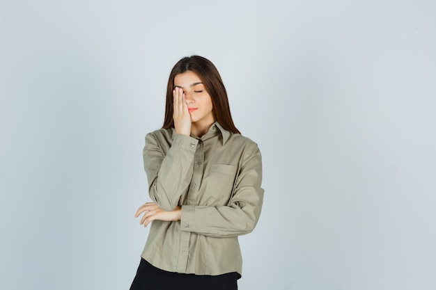 Młoda kobieta w koszuli, spódnicy, trzymając rękę na oku i wyglądająca na zmęczoną