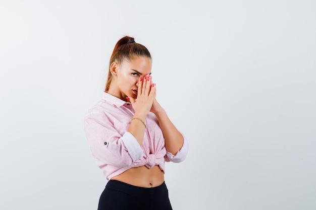 Młoda kobieta w koszuli, spodnie pokazujące splecione ręce w błagalnym geście