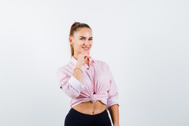 Młoda kobieta w koszuli, spodnie, trzymając rękę na brodzie i wyglądająca na szczęśliwą