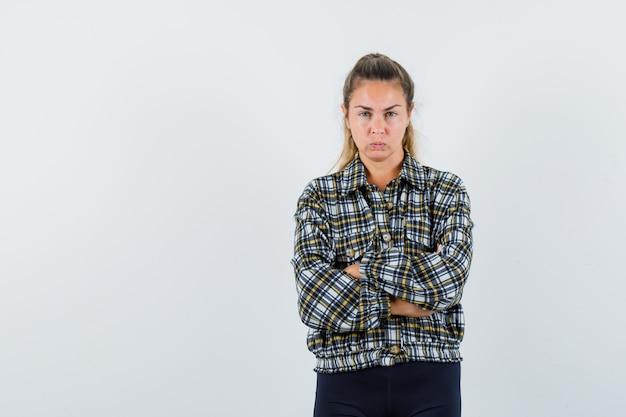 Młoda kobieta w koszuli, szorty, stojąc ze skrzyżowanymi rękami i patrząc poważnie, widok z przodu.