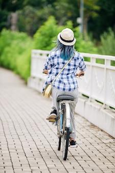 Młoda kobieta w koszuli w kratę i kapelusz, jazda na rowerze, widok z tyłu