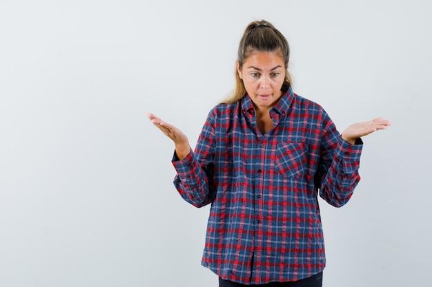 Młoda kobieta w koszuli w kratę wzrusza ramionami i wygląda na zaskoczoną