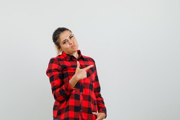 Młoda kobieta w koszuli w kratkę, wskazując na bok i patrząc pewnie, z przodu.