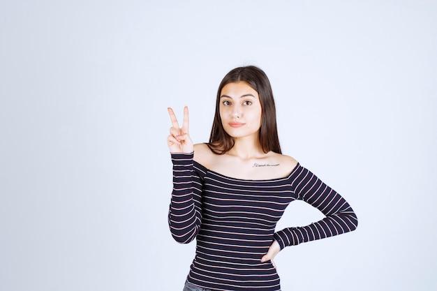 Młoda kobieta w koszuli w paski, wysyłając znak pokoju