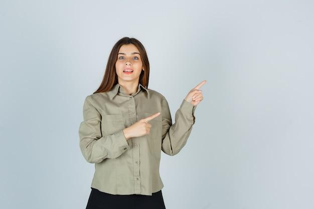 Młoda kobieta w koszuli ze spódnicą skierowaną w prawy górny róg i wyglądającą na zdumioną