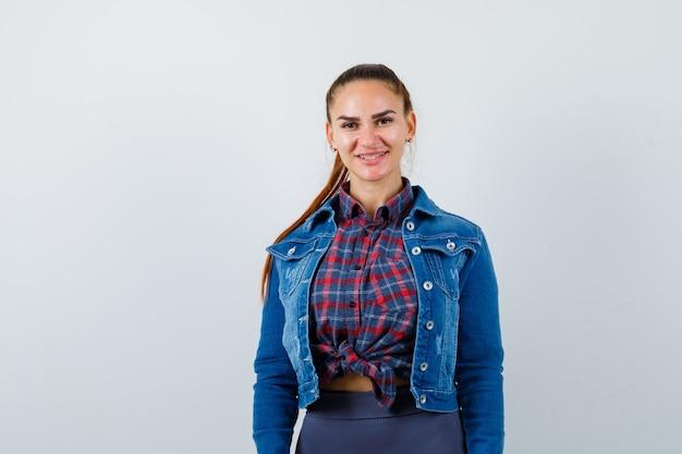 Młoda kobieta w kraciastą koszulę, kurtkę, spodnie i wyglądający uroczy, widok z przodu.