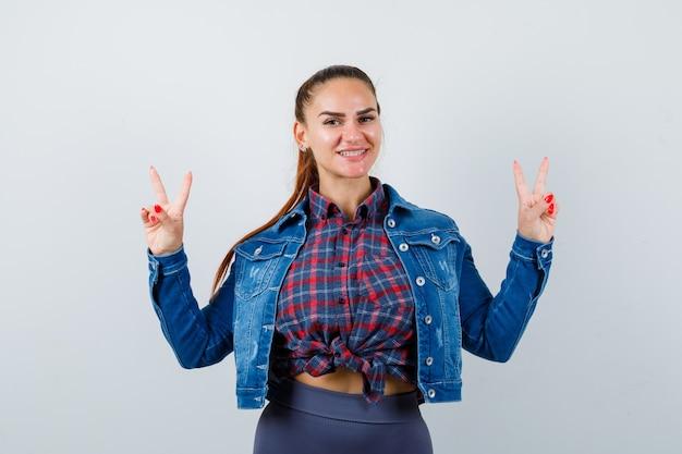 Młoda kobieta w kraciastej koszuli, kurtce, spodniach pokazujących znak zwycięstwa i patrząca błogo, widok z przodu.