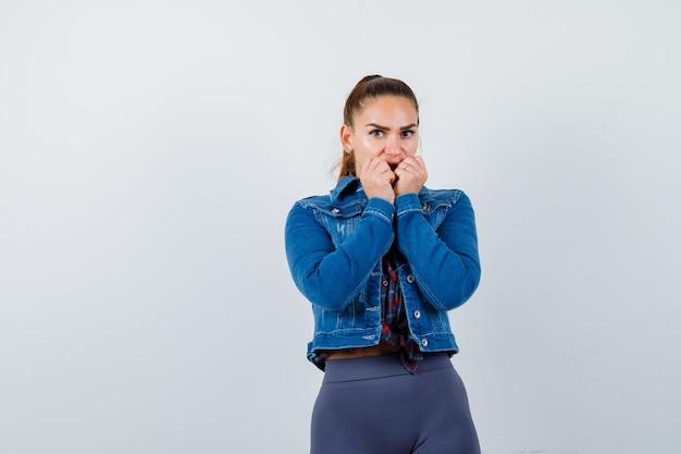 Młoda kobieta w kraciastej koszuli, kurtce, spodniach, stojąc w przerażonej pozie i patrząc zdziwiona, widok z przodu.