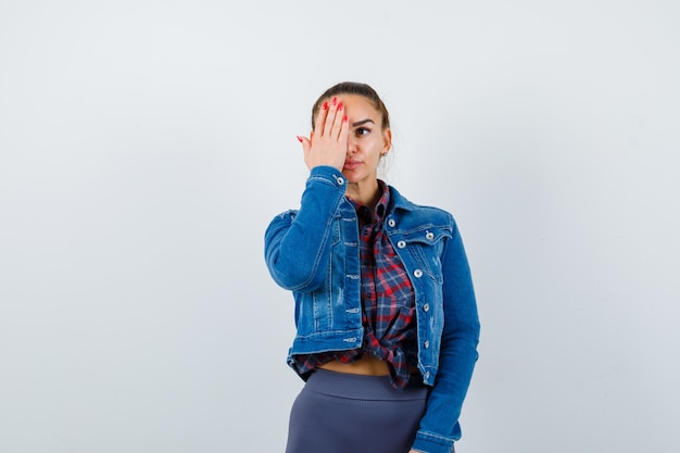 Młoda kobieta w kraciastej koszuli, kurtce, spodniach z ręką na oku i patrząc poważnie, widok z przodu.